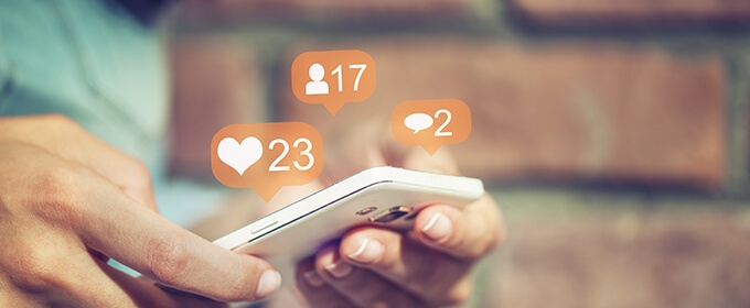 Somebody is holding a smartphone in his hands, while the numbers of likes, followers and comments of something display around the phone.