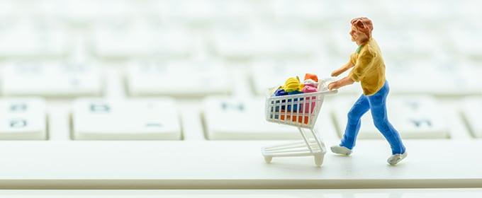 Figurine pushing a shopping cart over a keyboard.