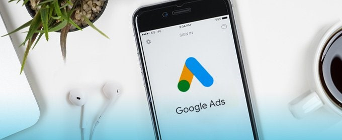 A smartphone with Google Ads app opened lying next to a cup of coffee and headphones.