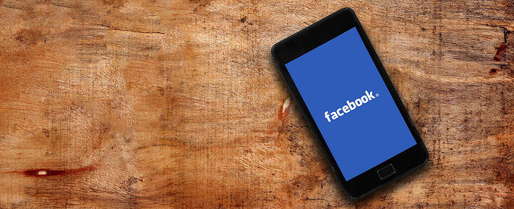 A smartphone with the facebook logo displayed on it lies on a wooden ground.