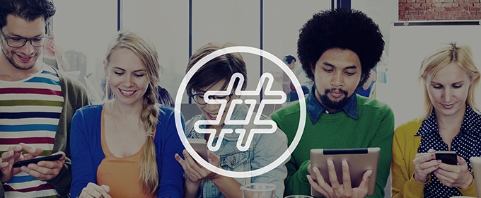 Five people sit together all looking at their mobile devices while the symbol of a hash is showing in the front.