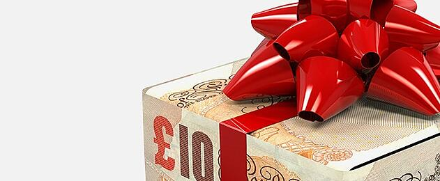 money shaped into a box with a red ribbon