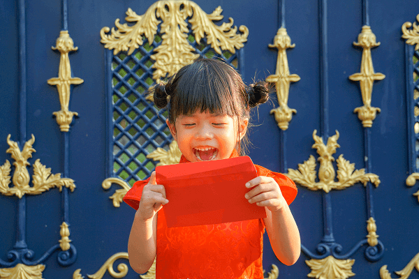 Young asian girl opening red envelope