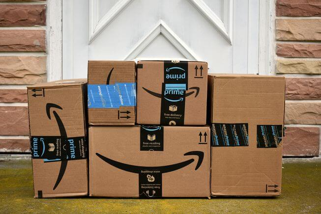 pile of amazon boxes in front of door