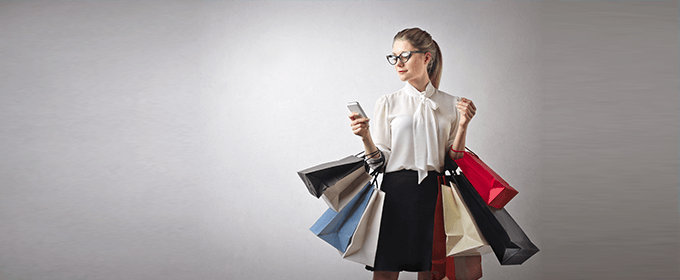 A woman carrying several shopping bags is looking at her smartphone.